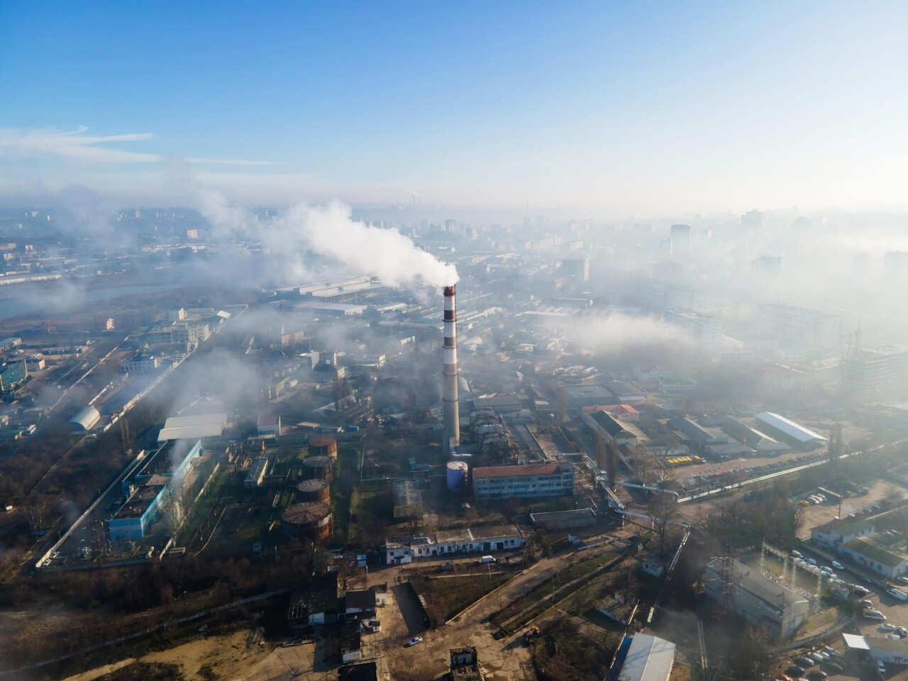 aerial-drone-view-chisinau-thermal-station-with-smoke-coming-out-tube-buildings-roads-fog-air-moldova-min.jpg